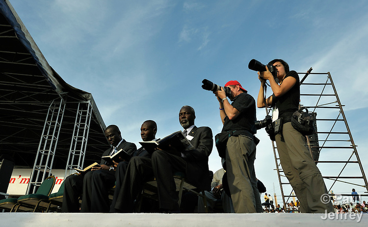 News photographers and religious leaders line up side-by-side on a stage in the national soccer stadium during an evangelical rally in Port-au-Prince, Haiti, held on the eve of the first anniversary of the January 2010 earthquake. The religious gathering featured Franklin Graham, the conservative U.S. evangelical leader.