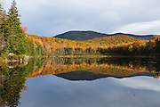 Reflection of autumn foliage in Kiah Pond in Sandwich, New Hampshire USA on a cloudy autumn day.