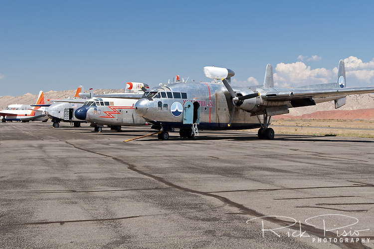 "Hawkins and Powers aircraft on the tarmac in Greybull, Wyoming, prior to auction in August of 2006. The C-119 Flying Boxcar still in the livery of the Amaroco Oil Company from the movie ""Flight of the Phoenix"" sits alongside a firefighting C-119 and a C-82 Packet."
