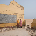Ghana - Dzita - Two schoolgirls stand on the ruins of their school. Two years ago, the Dzita EP Basic School had one of its four compounds destroyed by coastal erosion during the rainy season. Four classrooms were lost, forcing the school management to combine classes in order to shelter all the 670 students.
