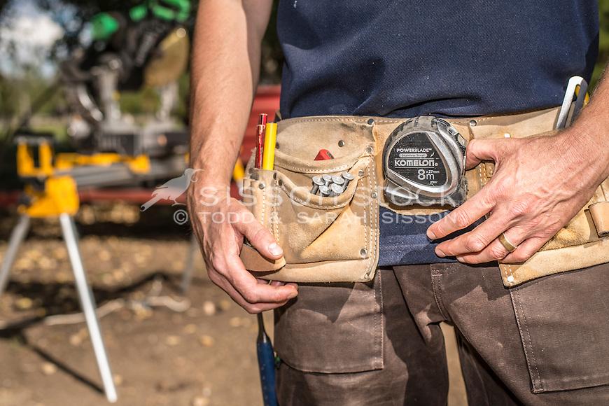 Home handyman wearing  tool belt, working outside on renovation project, New Zealand - stock photo, canvas, fine art print