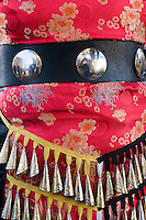 detail of red native American garment with baubles and bells