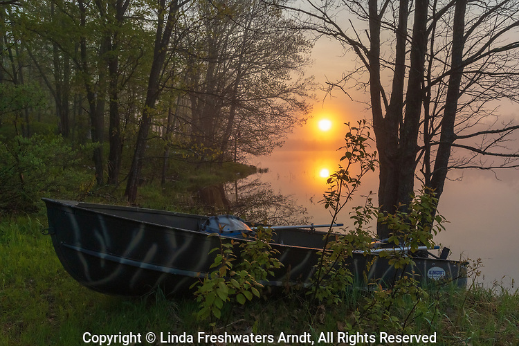 The sun begins to rise over an old fishing boat resting on the shore of a wilderness lake in northern Wisconsin.