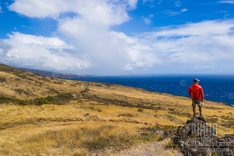 A man in a red jacket looks out the Pacific Ocean from a rocky outcrop in Kaupo along Piilani Highway, Maui.