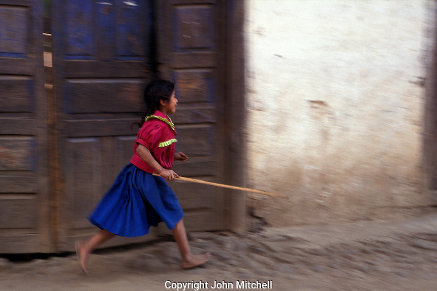 Purepecha or Tarascan girl running down a street in the village of Angahuan, Michoacan, Mexico
