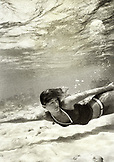 ARUBA, young woman swimming in Caribbean Sea (B&W)