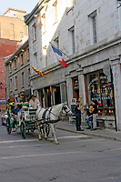 Tourists riding in a horse-drawn carriage or caleche on a street in Old Montreal, Quebec, Canada