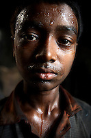 A child labourer working in a motor parts factory in old Dhaka.