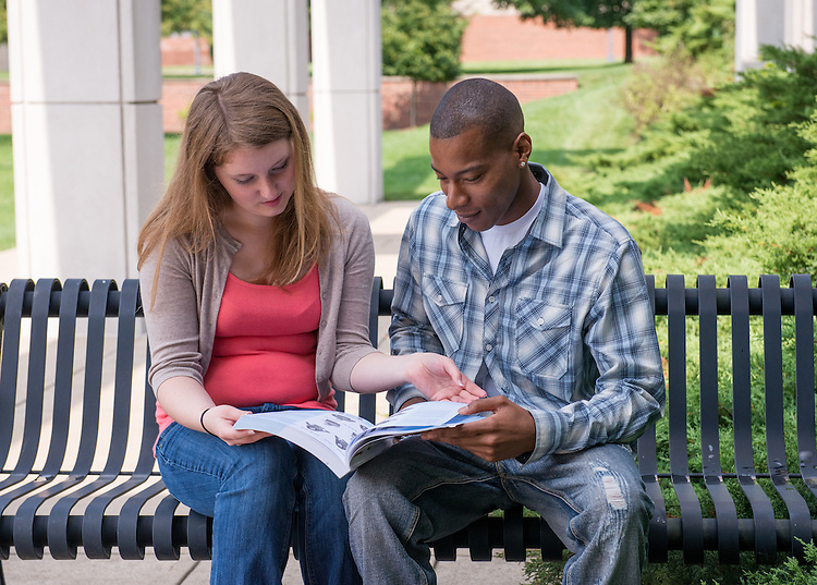 Courtney Barker, left, and Chris Jones, right, share a book on American sign language outside of the Ohio University Zanesville bookstore.