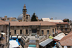 A rooftop view of the Christian Quarter in the Old City of Jerusalem.  At left is the minaret of the Mosque of Omar with the grey domes of the Church of the Holy Sepulchre behind it.  The Old City of Jerusalem and its Walls - UNESCO World Heritage Site