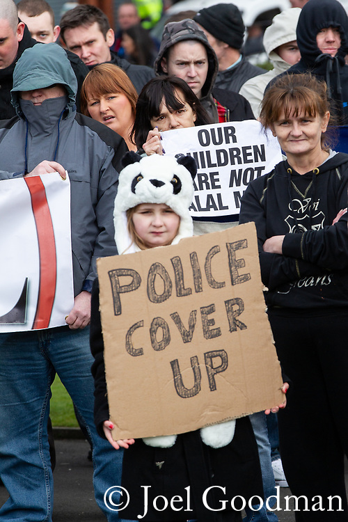 "© Joel Goodman - 07973 332324 . 03/03/2012 . Heywood , UK . A young girl holds up a sign that reads "" Police cover up "" . The National Front hold a rally in protest against an alleged paedophile ring that had been operating in the area . There is currently (3rd March 2012) a case being tried at Liverpool Crown Court in relation to the allegations . Last Thursday (23rd February 2012) a protest organised in the town in relation to the same story resulted in Asian business being attacked by an angry mob . Photo credit : Joel Goodman"