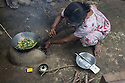 India – West Bengal: Mina Sharma, 45, cooking outside her home at Mogulkata Tea Estate, in the Dooars region. Workers have 2 hours lunch break during which they have to run back home, few km away from the fiels, cook, eat quickly and run back to the fields again when the bell rings. The woman started working as a plucker when she was 30, after taking over her mother's job. Sharma still lives with her parents in the family house the tea company built more than 50 years ago.