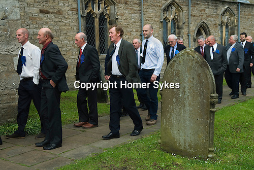 Askrigg Equitable Benevolent and Friendly Society. Askrigg north Yorkshire UK. The annual walk to church behind the Friendly Society banner starts from outside the Kings Arms Hotel. Honorary members wear white rosettes while ordinary members wear blue