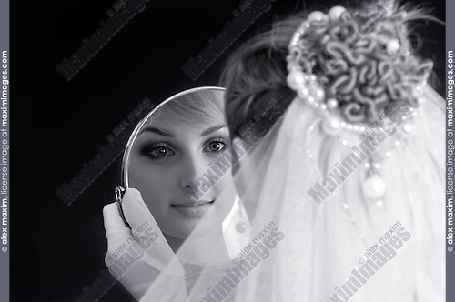 Stock photo of a Young beautiful bride wearing a white wedding dress and a veil admiring herself in a looking-glass artistic conceptual portrait Twenty year old caucasian woman Isolated on dark red background Black-white