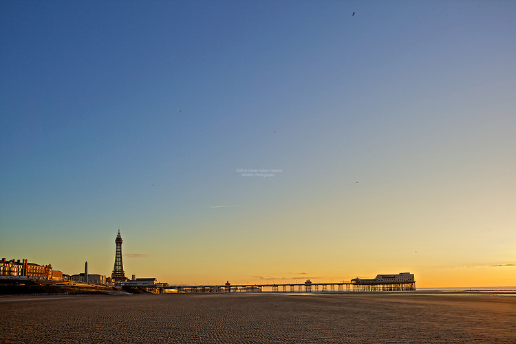 Golden winter Sunlight bathes Blackpool tower and the North Pier.