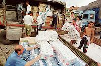 In der Ortschaft Orahovac lebten vor dem Kosovo-Krieg Kosovo-Serben und Kosovo-Albaner zusammen. Nun ist die serbische Bevoelkerung vor den Kosovo-Albanern in den oberen Teil des Ortes gefluechtet. Hinzu kamen etliche Fluechtlinge aus den Bergen und der Umgebung. Mittlerweile leben nahezu 3.500 Menschen auf engstem Raum.<br /> Hier: Bewohner der Enklave entladen Hilfsgueter, welche mit einer Hilfskonvoi des jugoslawischen Roten Kreuz aus Belgrad gekommen sind.<br /> Orahovac/Jugoslawien, 2.8.1999<br /> Copyright: Christian-Ditsch.de<br /> [Inhaltsveraendernde Manipulation des Fotos nur nach ausdruecklicher Genehmigung des Fotografen. Vereinbarungen ueber Abtretung von Persoenlichkeitsrechten/Model Release der abgebildeten Person/Personen liegen nicht vor. NO MODEL RELEASE! Don't publish without copyright Christian-Ditsch.de, Veroeffentlichung nur mit Fotografennennung, sowie gegen Honorar, MwSt. und Beleg. Konto: I N G - D i B a, IBAN DE58500105175400192269, BIC INGDDEFFXXX, Kontakt: post@christian-ditsch.de<br /> Urhebervermerk wird gemaess Paragraph 13 UHG verlangt.]