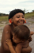 Roraima, Brazil. Laughing Yanomami woman with flower ear plugs holding her child.