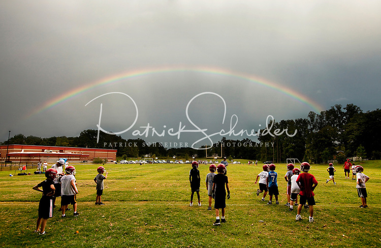 A rainbow appears in the sky during a rainy football practice. Each fall football season, youths across the United States pull on helmets and strap on pads to play American football, one of the country's most popular sports. The Pop Warner football league has been helping youngsters play the sport since 1929. Photo is part of a series of images documenting one team of North Carolina boys learning and playing the sport in Cornelius, NC in fall 2009. They're playing on the Lake Norman Giants.