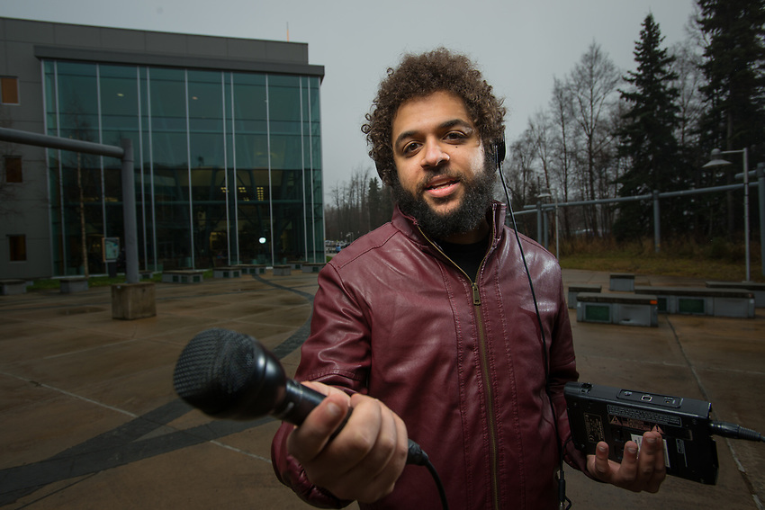 UAA Journalism Alum and Alaska Public Radio Network web editor Wesley Early has his portrait taken outside the Consortium Library.