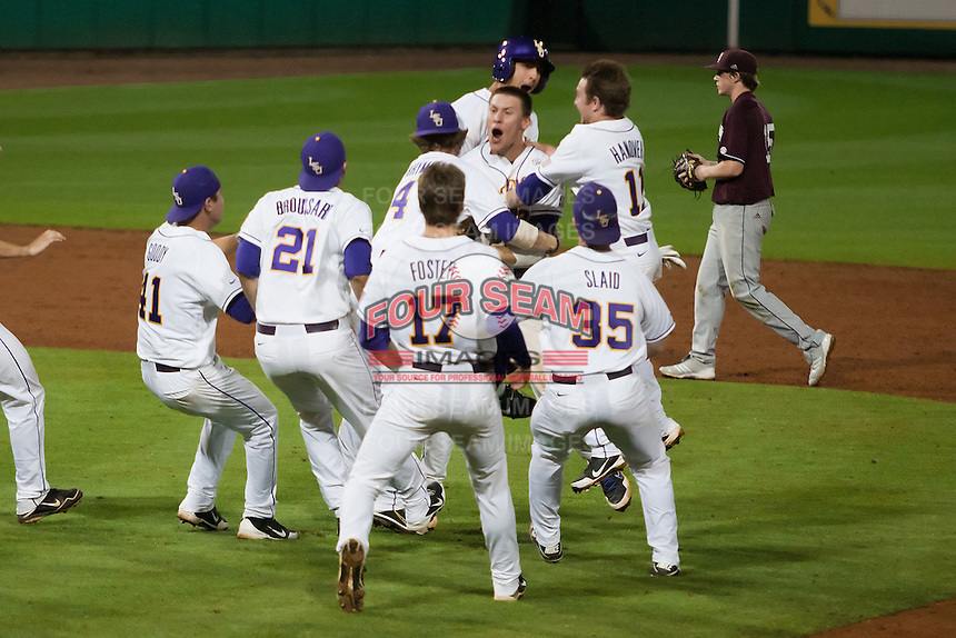 The LSU Tigers mob JaCoby Jones #23 after he drove in the winning run in the bottom of the 10th inning against the Mississippi State Bulldogs during the NCAA baseball game on March 16, 2012 at Alex Box Stadium in Baton Rouge, Louisiana. LSU defeated Mississippi State 3-2 in 10 innings. (Andrew Woolley / Four Seam Images)..