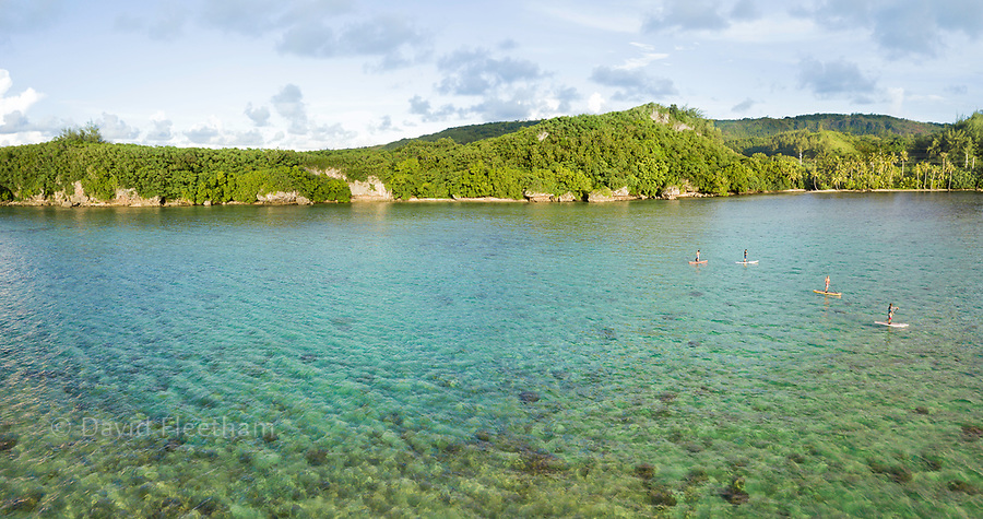An aerial panorama of four people on stand-up paddle boards on a calm day in Piti Bay, Guam, Micronesia, Mariana Islands, Pacific Ocean.
