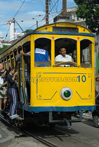 Bonde, Rio's famous electric tram at the stop Largo do Guimaraes; Rio de Janeiro, Espirito Santo, Brazil. The historic street railway has been transporting Rio residents for over a century. The little yellow tram rattles along the track like an antique roller coaster. Starting from downtown Carioca Station across the Arcos da Lapa (a former aqueduct) it is riding through the neighborhood of Santa Teresa. Seating is on wooden benches, but the local daredevils prefer swinging from the tram's outer poles. --- No releases available.