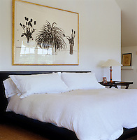 A large pen and ink drawing hangs above the double bed in the master bedroom