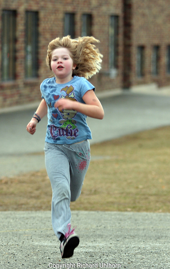 A young girl running across a school yard.