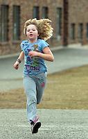 A young girl running across a school yard.