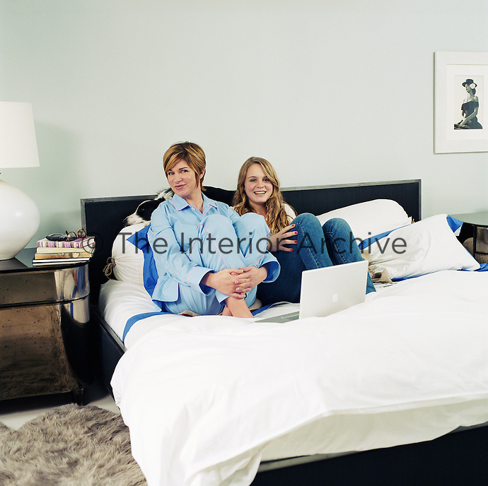 Portrait of interior designer Sharon Simonaire and her teenage daughter sitting in her bed
