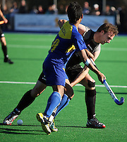 NZ's Ryan Archibald tackles Faizal Saari during the international hockey match between the New Zealand Black Sticks and Malaysia at Fitzherbert Park, Palmerston North, New Zealand on Sunday, 9 August 2009. Photo: Dave Lintott / lintottphoto.co.nz