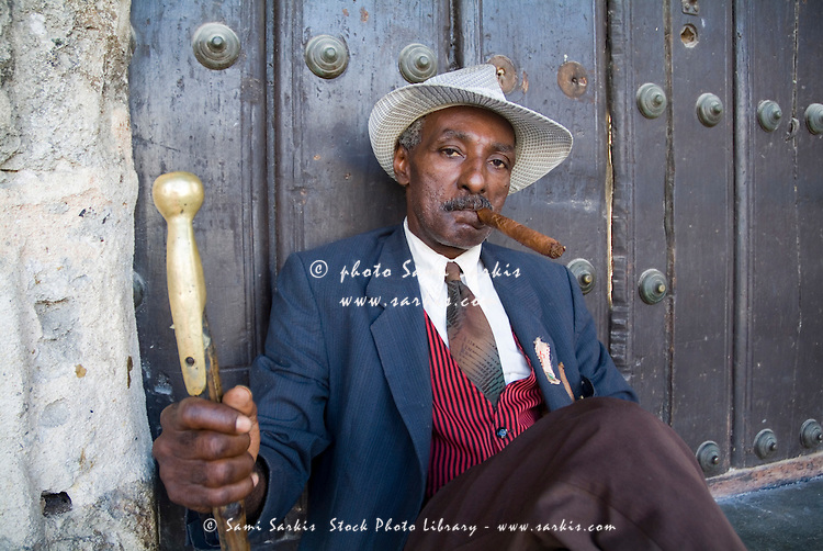 Portrait of a man wearing a 1930s-style suit and smoking a cigar, Havana Cuba.