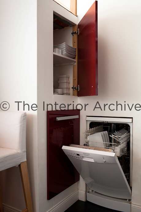 The walls of the kitchen are fitted with deep cupboards and a small dishwasher