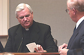 Monsignor William V. Sullivan, pastor of St. Ann's Catholic Church in Ashland, Virginia, looks at a note he took during a call about the sniper shootings during his testimony in the trial of sniper suspect John Allen Muhammad in courtroom 10 at the Virginia Beach Circuit Court in Virginia Beach, Virginia on October 30, 2003. <br /> Prince William County (Virginia) prosecutor Paul Ebert is at right. <br /> Credit: Adrin Snider - Pool via CNP