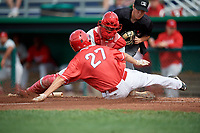 Auburn Doubledays catcher Wilmer Perez (45) tags out Davis Bradshaw (27) as he slides home as home plate umpire Roberto Pattison looks on during a game against the Batavia Muckdogs on September 2, 2018 at Dwyer Stadium in Batavia, New York.  Batavia defeated Auburn 5-4.  (Mike Janes/Four Seam Images)