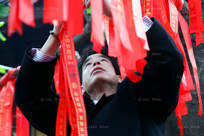 A man ties red ribbons written with well wishes onto a tree at Longhua Temple in Shanghai, China on 26 January, 2009.   Traditionally the first day of the lunar new year is an auspicious day to offer prayers and honor ancestors.