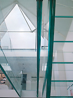 A view up through the angular glass staircase and bridge, which crosses the triple height atrium, to the vast triangular skylight