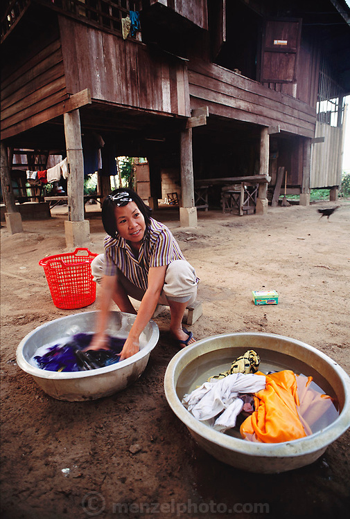 Buaphet Khuenkaew washes her family's clothes in wash basins on the ground near her house. Published in Material World page 85. She and her family live in the wooden 728-square-foot house on stilts, surrounded by rice fields in the Ban Muang Wa village, outside the northern town of Chiang Mai, in Thailand.
