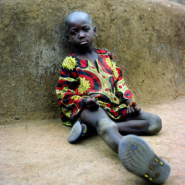 A young boy sitting in the floor.