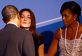 Pittsburgh, PA - September 24, 2009 -- United States President Barack Obama (L) kisses French President Nicolas Sarkozy's wife Carla Bruni Sarkozy (C) while welcoming her to the opening dinner for G-20 leaders with U.S. first lady Michelle Obama at the Phipps Conservatory on Thursday, September 24, 2009 in Pittsburgh, Pennsylvania. Heads of state from the world's leading economic powers arrived today for the two-day G-20 summit held at the David L. Lawrence Convention Center aimed at promoting economic growth. .Credit: Win McNamee / Pool via CNP