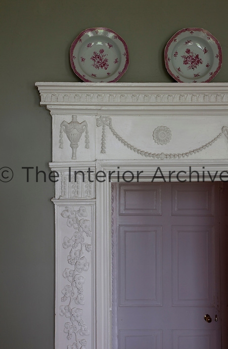Intricately sculpted stucco grape vines wind their way up to urns and classical swags on a door frame in the drawing room