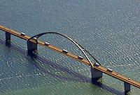 Fehmarnsund: EUROPA, DEUTSCHLAND, SCHLESWIG- HOLSTEIN, 21.06.2010: Der Fehmarnsund ist die Meerenge zwischen der drittgroessten Deutschen Ostseeinsel Fehmarn und dem Festland von Schleswig- Holstein.  Die Fehmarnsundbruecke verbindet die Insel Fehmarn in der Ostsee mit dem Festland bei Großenbrode..Die 963 Meter lange kombinierte Straßen- und Eisenbahnbruecke ueberquert den 1.300 Meter breiten Fehmarnsund, hat eine lichte Hoehe von 23 Metern ueber dem Mittelwasser und wurde 1963 in Betrieb genommen. Zeitgleich wurde die Faehrlinie von Großenbrode-Kai nach Gedser durch die Faehrlinie Puttgarden-Rødby (Daenemark) ersetzt. Durch die Fehmarnsundbruecke und den gleichzeitig gebauten Faehrhafen Puttgarden auf Fehmarn wurde die durchschnittliche Reisezeit auf der so genannten Vogelfluglinie von Hamburg nach Kopenhagen deutlich verkuerzt. Eine schnellere Verbindung wird geplant.