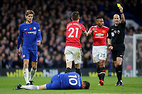 Eden Hazard of Chelsea awaits treatment as Ander Herrera receives a yellow card from referee, Anthony Taylor, for his challenge on the Chelsea player during Chelsea vs Manchester United, Premier League Football at Stamford Bridge on 5th November 2017