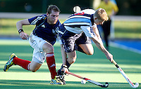 Rick Gay (L) of East Grinstead tackles Will Naylor during the England Hockey League Mens Premier Division game between Hampstead & Westminster against East Grinstead at The Paddington Recreation Ground, Maida Vale on Sun Oct 10, 2010
