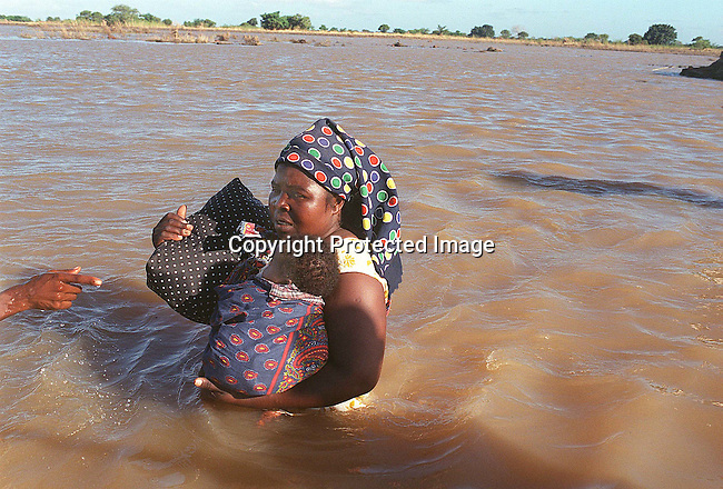 A woman crossing a flooded area in Treis Febrero , 150 km north of Maputo with her baby; Mozambique; floods; relief work..©Per-Anders Pettersson/iAfrika Photos