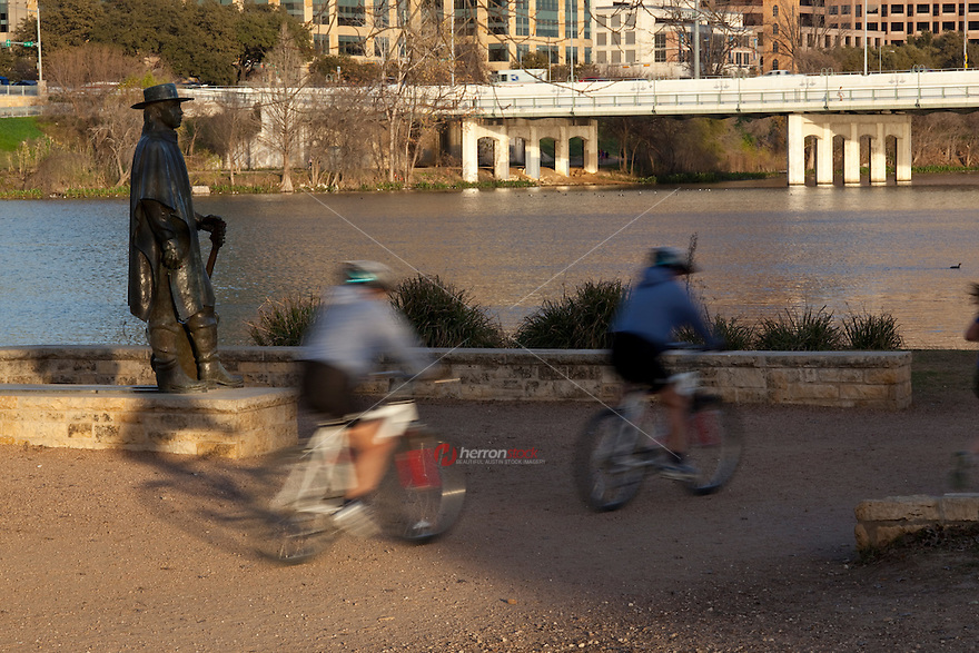 Bike riders zoom up and down the Lady Bird Lake hike and bike trail, past the Stevie Ray Vaughan Memorial Statue