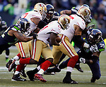 Seattle Seahawks  defensive end Michael Bennett (72) grabs ahold of San Francisco 49ers running back Frank Gore (21) during the first quarter  at CenturyLink Field in Seattle, Washington on December 14, 2014. The Seahawks beat the 49ers 17-7.    © 2014. Jim Bryant Photo. All Rights Reserved.