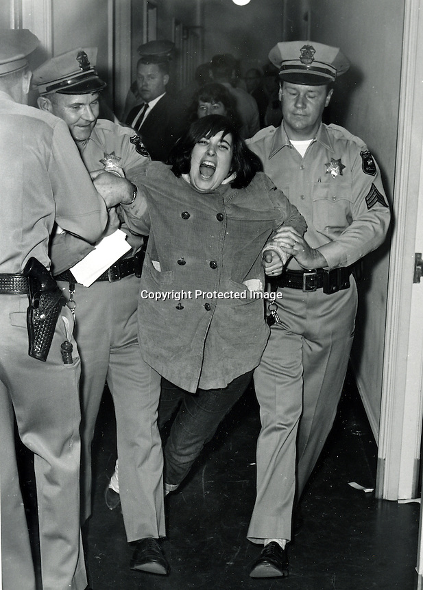 "SIT-IN AT SPROUL HALL, University of California at Berkeley. One of the students is carried out by U.C Police. Students were protesting the ""Free Speech"" issue at the University. (1964 photo by Ron Riesterer)."