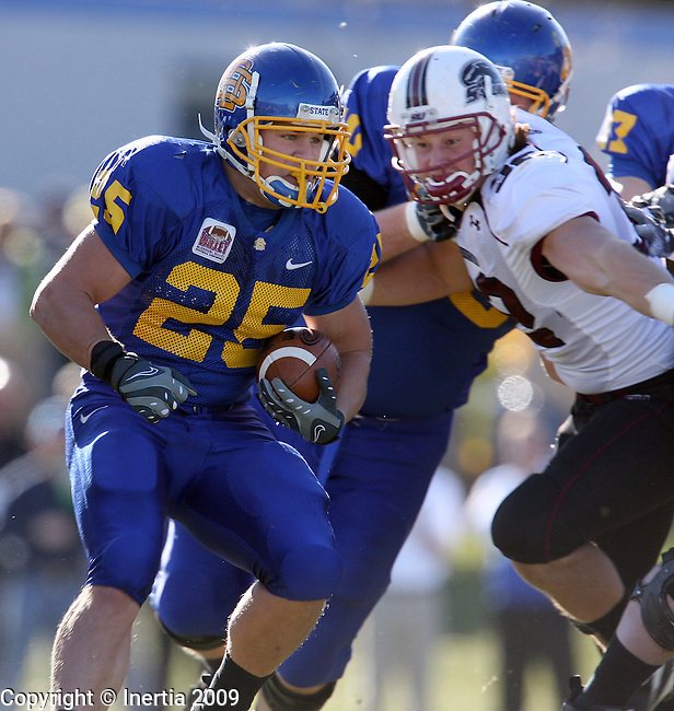 BROOKINGS, SD - NOVEMBER 7:  Tyler Duffy #25 of South Dakota State University breaks through the line for a short gain past Dolapo Adubifa #92 of Southern Illinois in the first quarter of their Missouri Valley Conference game Saturday afternoon at Coughlin Alumni Stadium in Brookings. (Photo by Dave Eggen/Inertia).