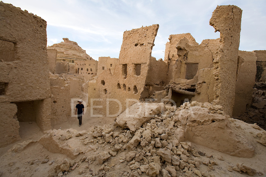 A man in his early 30's, walks within walls of the 13th century mud-brick fortress of Shali, at sunset, in Siwa Town of the Siwa Oasis, near the Libyan border in Egypt.